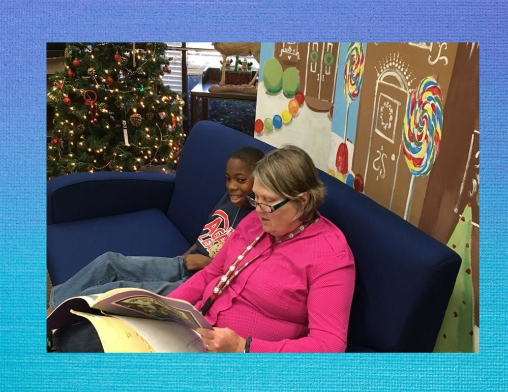 A teacher reads to a student in the media center.